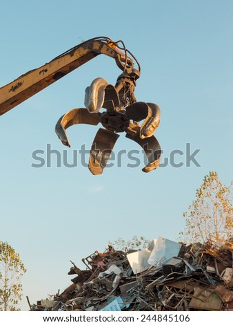 crane with open claw on top of pile with scrap metal - stock photo