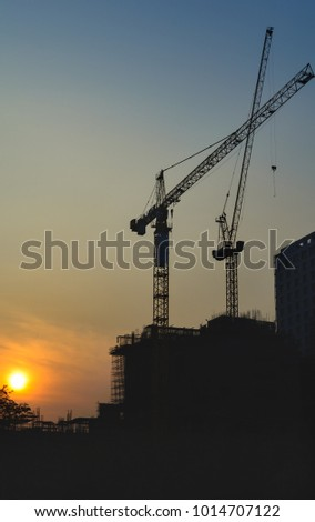 Cranes and building under construction crane tower equipment at construction site in sunrise.