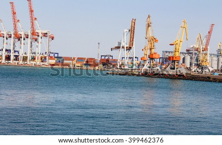 Cranes and cargo containers at port, beautiful sea
