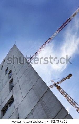 Cranes and concrete building on a construction site in France