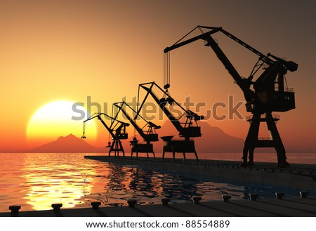 Cranes at a port at sunset.
