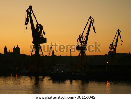 Cranes at commercial dock at sunset time (Malta, Maltese islands)