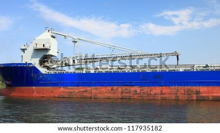 cranes in a port loading a ship coal - stock photo