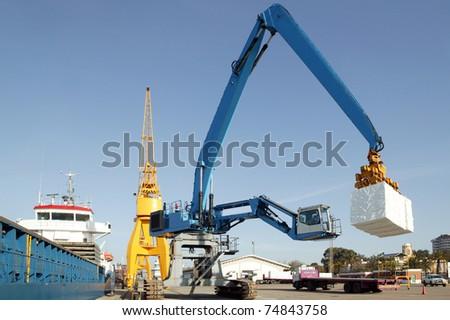 Cranes in a port, unloading a ship - stock photo