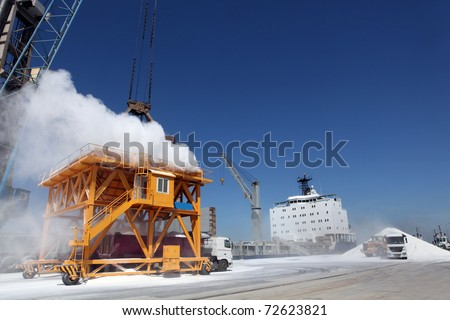 Cranes in a port, unloading a ship of urea. - stock photo