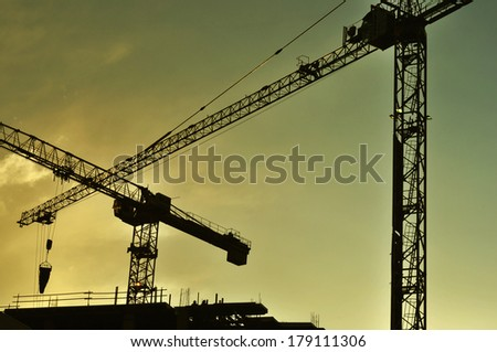 Cranes on construction site in the sunset, silhouettes with some detail - stock photo