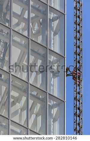 Cranes on Skyscraper under construction - stock photo