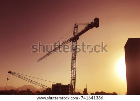 Cranes over new construction site as sun sets
