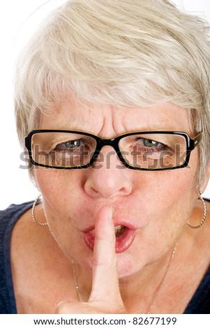 Cranky, mature woman shushing to get quiet. - stock photo