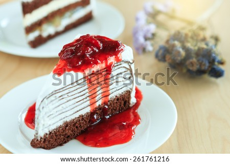 crape cake with strawberry sauce on white plate. (Selective Focus) - stock photo