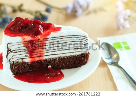 crape cake with strawberry sauce on white plate. (Selective Focus)