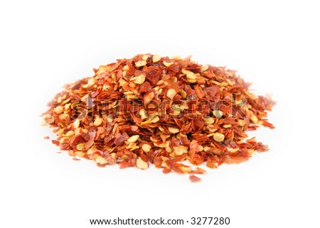 Crashed chilli pepper, isolated on white. Shallow depth of field, focused on the centre of the pile. - stock photo