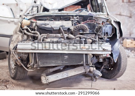 Crashed silver car with broken roof, front view. - stock photo