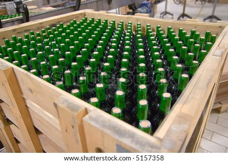 Crate of wine bottles maturing, with some cobwebs across bottles. - stock photo