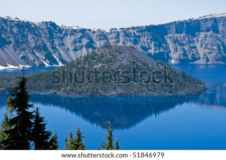 Crater Lake in Oregon with a perfect reflection on a calm sunny day - stock photo