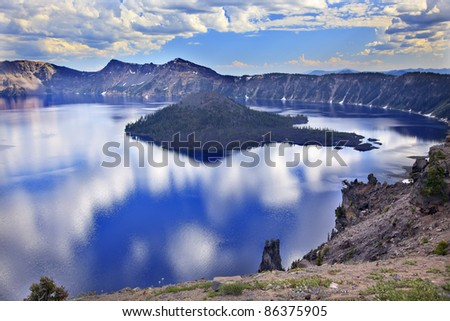 Crater Lake Reflection, Wizard Island, Clouds Blue Sky Oregon Pacific Northwest - stock photo