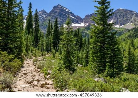 Crater Lake Trail - A rugged hiking trail winding through a pine forest at base of Maroon Bells, Aspen, Colorado, USA. - stock photo