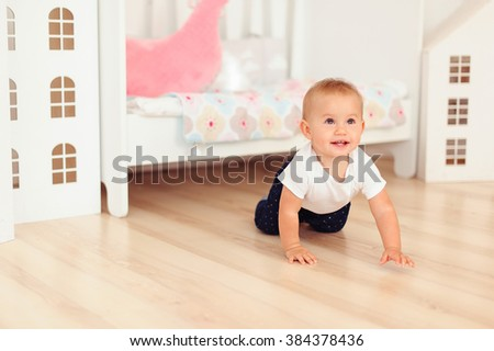 crawling baby girl at kids room on floor - stock photo