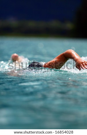 Crawling Young man swimming in a lake with professional gear on. Ideal shot for summer / vacation. - stock photo