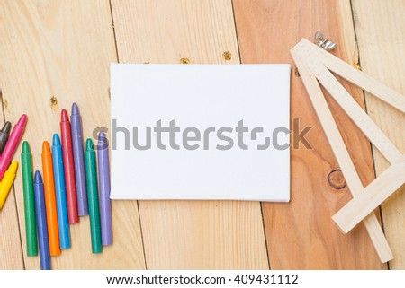 Crayon color with paint canvas stand on wood background with copy space - stock photo