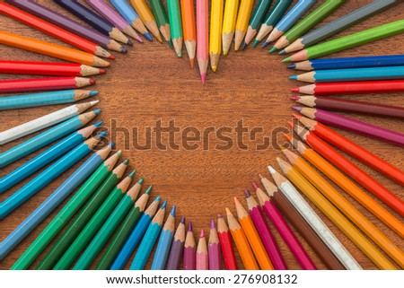 Crayon heart - Heart shape made of colored pencils - stock photo