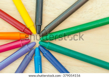 Crayon on wood background with copy space - stock photo