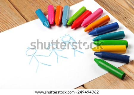 Crayons lying on a paper with children's drawing family. Selective focus, copy space background - stock photo