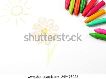 Crayons lying on a paper with children's drawing flower and sun. Selective focus, copy space background - stock photo