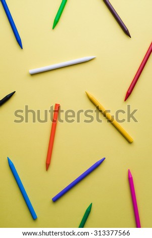 Crayons of different colors over a yellow background - stock photo