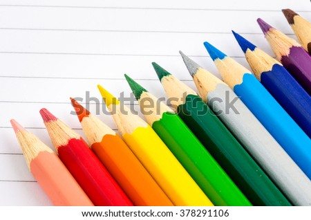 Crayons on a Notebook. Back to School Concept. Shallow Deep of Field.