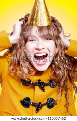 Crazy and overjoyed party girl in a gold party hat laughing in merriment as she runs her hands through her wavy blonde hair - stock photo