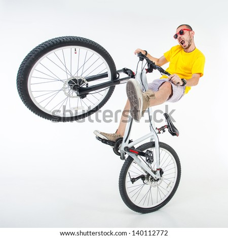 crazy boy on a dirt jump bike isolated on white - wide studio shot - stock photo