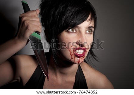 Crazy cannibal woman with blood on her face and knife in hands - stock photo