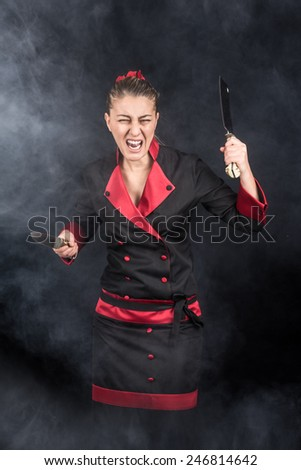 Crazy chef screaming and attacking with her weapons knife and chopping knide between smoke and fog - stock photo