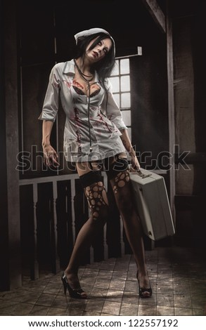 Crazy dead nurse with medical case in dark room - stock photo