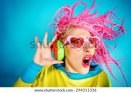 Crazy expressive trendy DJ girl in bright clothes, headphones and bright dreadlocks. Disco, party. Bright fashion. - stock photo