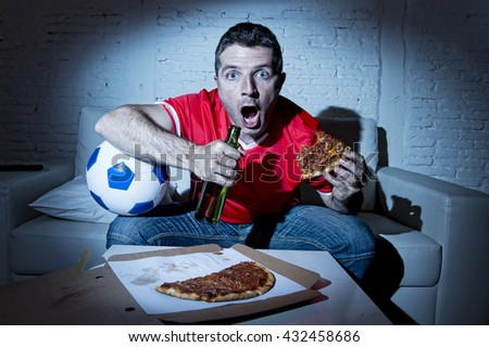 crazy fanatic man football fan watching football game on television wearing red team jersey nervous and surprised on sofa couch at home holding  soccer ball drinking beer eating pizza - stock photo