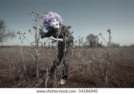 Crazy funny man outdoors in the steppe. Artistic colors added - stock photo