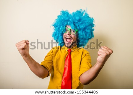 crazy funny young man with blue wig on white background - stock photo
