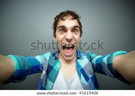 Crazy guy screaming at camera while shaking it, fool's day series - stock photo