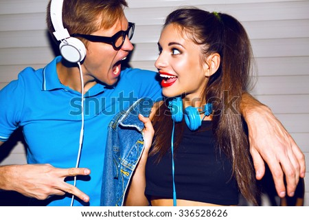 Crazy hipster couple having fun, screaming singing and smiling, looking to each other , having fun at romantic date, listening music at big headphones, trendy bright clothes. - stock photo
