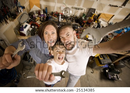 Crazy Hispanic family in garage with crescent wrenches - stock photo