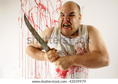 Crazy insane butcher covered with blood.  Harsh lighting for more disturbing feel. Slight motion blur on arms and knife. - stock photo