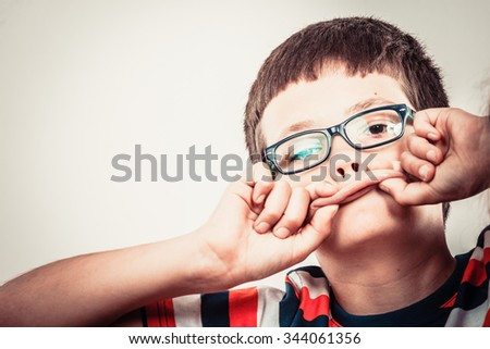 Crazy kid little boy making silly face expression. Childhood fun. - stock photo