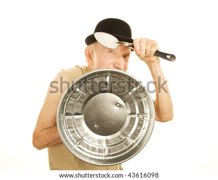 Crazy man defending himself with trashcan lid and metal spoon - stock photo