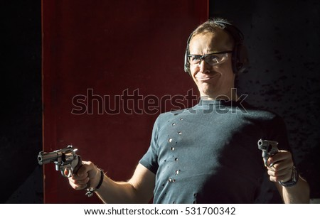 Crazy man in a headphones with a gun in his hand on the dark background