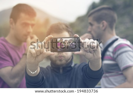 Crazy man taking selfie with friends - stock photo