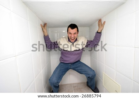 crazy man trapped in a corner - stock photo