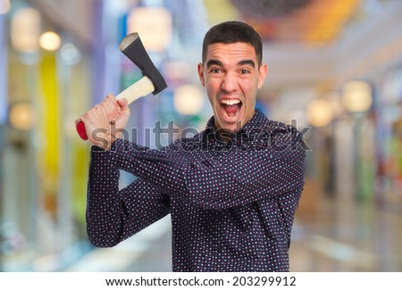 crazy man with an ax in a shopping center - stock photo