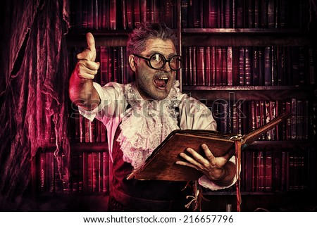 Crazy medieval scientist working in his laboratory with old manuscripts. Alchemist. Halloween. - stock photo